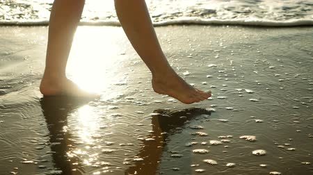 blote voeten : Close-up shot of bare feet. Woman walking across the sandy beach of Mediterranean sea. Greece. Slow motion. HD