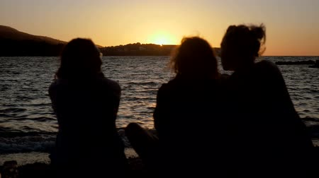 homokóra : Silhouette of three women sitting on shore of Mediterranean sea, drinking an alcoholic drink, looking at sea in the sunset. Greece. Slow motion. HD Stock mozgókép