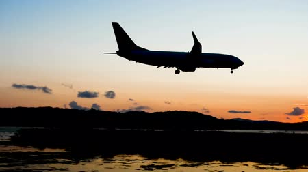 kerkyra : Passenger airplane flying in sky. Silhouette of aircraft landing on runway at airport of Corfu in dusk. Greece. Slow motion. HD