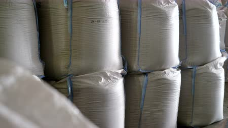 storing : Big white plastic bags with cereal crops: rye, wheat, barley are storing on warehouse. 4K Stock Footage