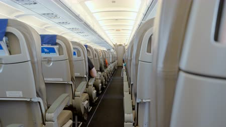 aircrew : The interior of the aircraft. Rows of seats on the plane with passengers on board. 4K