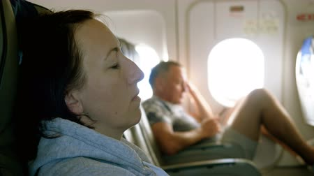 lugares sentados : Handsome man sitting at porthole in plane. Beautiful woman sleeping in passenger seat inside an airplane. 4K