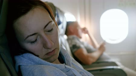 jet out : Handsome man sitting at porthole in plane. Beautiful woman sleeping in passenger seat inside an airplane. 4K