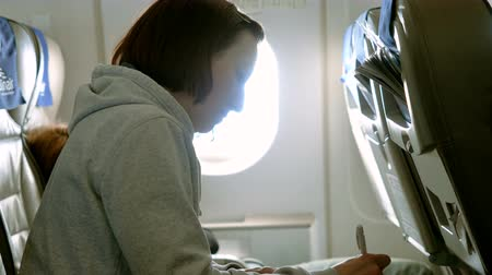 pero : An attractive woman making notes in a notebook, sitting in a seat by the window on airplane. 4K