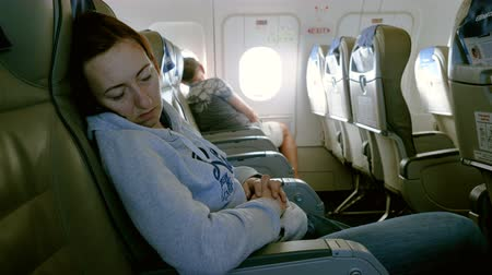 corredor : Handsome man sitting at porthole in plane. Beautiful woman sleeping in passenger seat inside an airplane. 4K