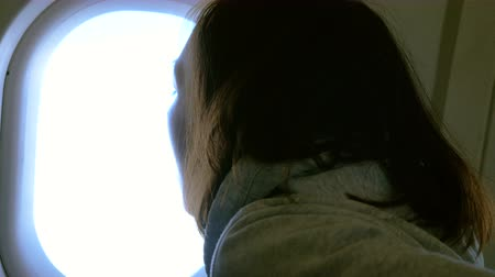 jet out : Girl at porthole on plane. Young woman seating on passenger seat and looking out window on airplane. 4K Stock Footage