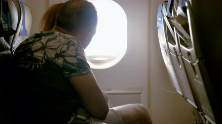 jet out : Adult couple in love at porthole on plane. Woman and man seating on passenger seat and looking out window on airplane. 4K