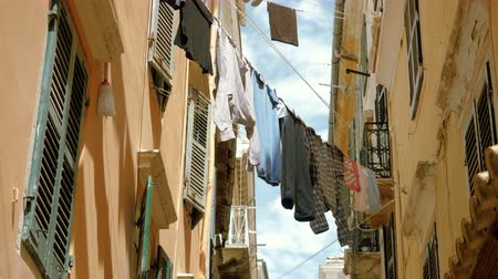 trousers : Clean clothes: t-shirts, trousers, shirts and linen hanging on a thin rope to dry outdoors in streets of Kerkyra. Corfu. Greece. 4K
