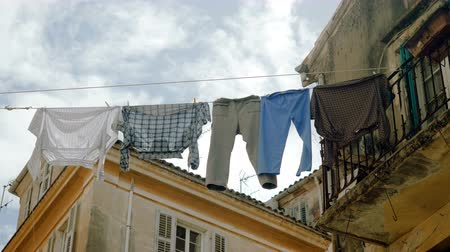 szárítókötél : Clean clothes and linen hanging on a clothesline to dry outdoors in streets of Kerkira. Corfu. Greece. 4K