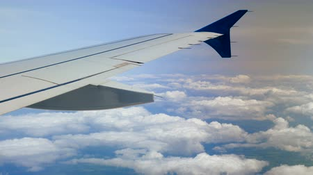 Aeroplane. View of airplane wing of aircraft flying above the clouds. 4K Stock Footage