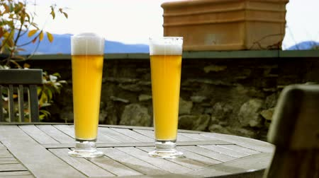 quartilho : Close-up shot of two pints of beer standing on the wooden table in a modern restaurant. 4K