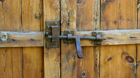 защелка : Close-up shot of wooden door locked with the metal latch. 4K