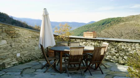 veranda : Wooden table and six chairs with folded umbrella on veranda of the restaurant overlooking the mountains. 4K Dostupné videozáznamy