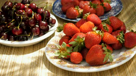 gıda maddesi : Juicy fruit. Close-up shot of fresh strawberries and sweet cherries on plates. 4K Stok Video