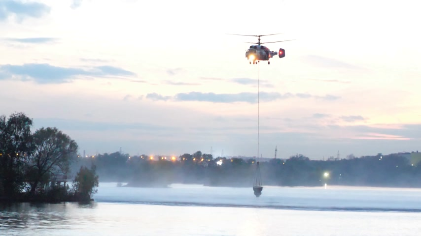 mi : The helicopter collects water in the river to extinguish a fire. The rescue service and firefighters extinguish the fire. The helicopter hovered in the air. Fire in Moscow, Russia. Military helicopter Stock Footage