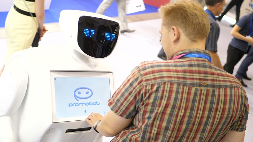 intelligencia : Novosibirsk Russia - June 29 2017: Robot communicates with people at exhibitions. Robot with interactive display communicates with visitors in a business centre. People using his touch screen