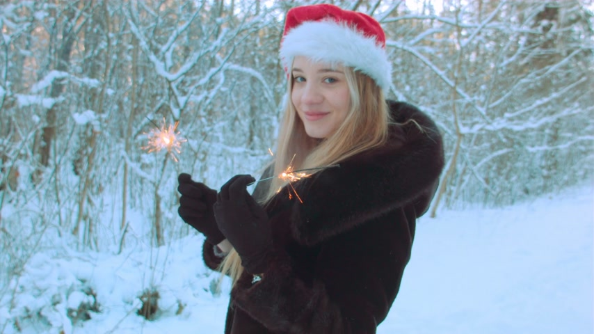 snowfield : Woman with Santa hat holding sparklers Stock Footage