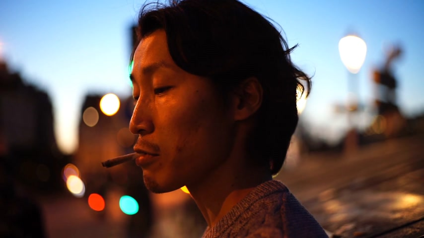 cigarette : Close-up of asian man smoking in a city at dusk Stock Footage