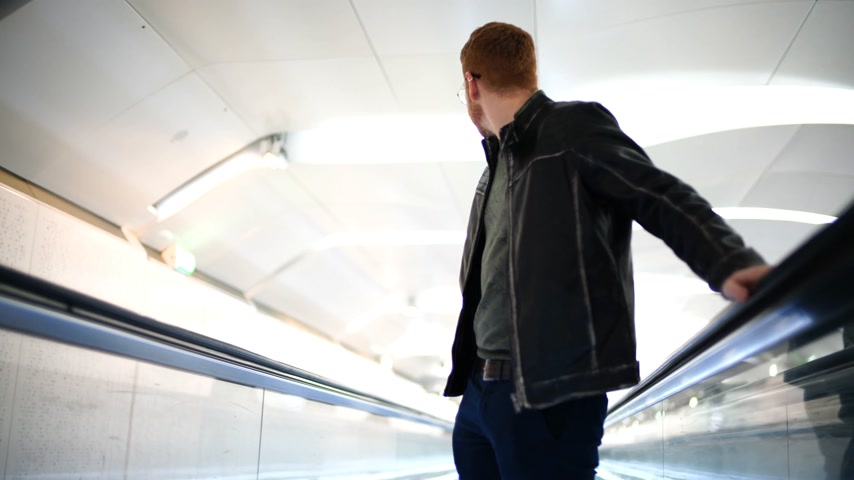 commute : Man traveling on a moving walkway