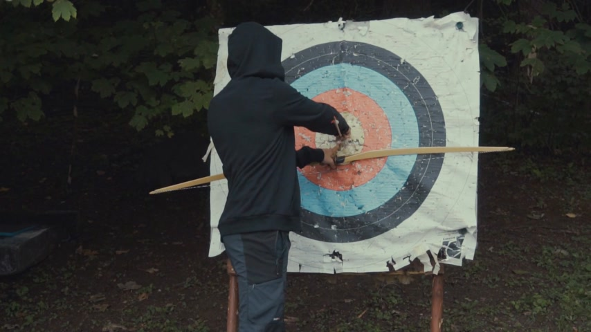 tiro com arco : Man pulling out an arrow from the target board Stock Footage