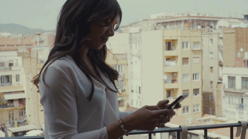 mulheres adultas meados : Woman texting on her phone on the balcony Vídeos