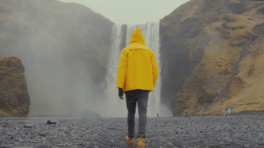 gushing : Person with raincoat walking towards a waterfall
