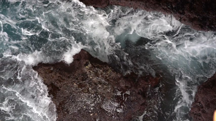 gushing : Waves hitting against a rocky shore
