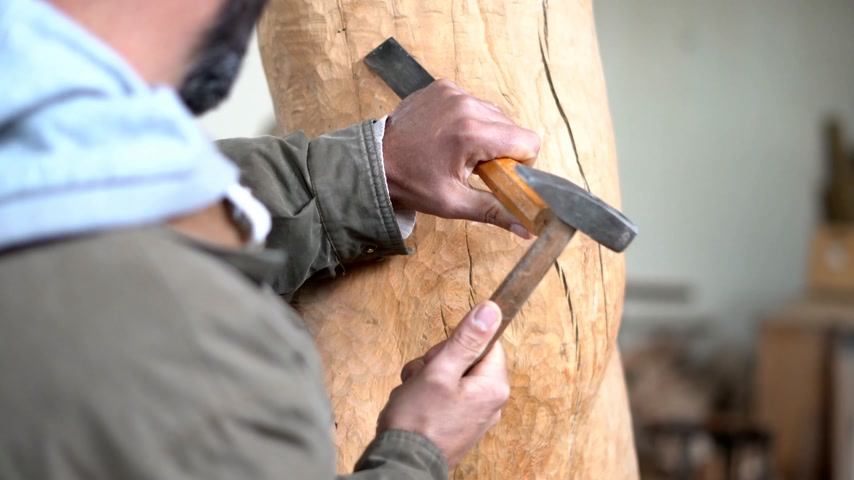 handig : Man carving a wooden trunk Stockvideo