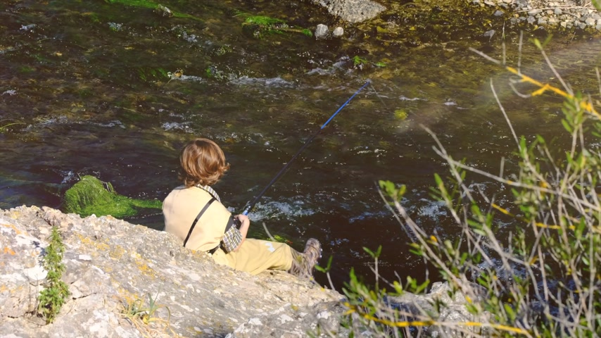 gushing : Boy fishing by the river Stock Footage