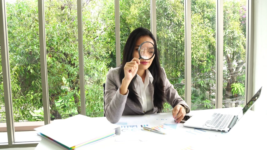 Asian business female review document with magnifying at office building