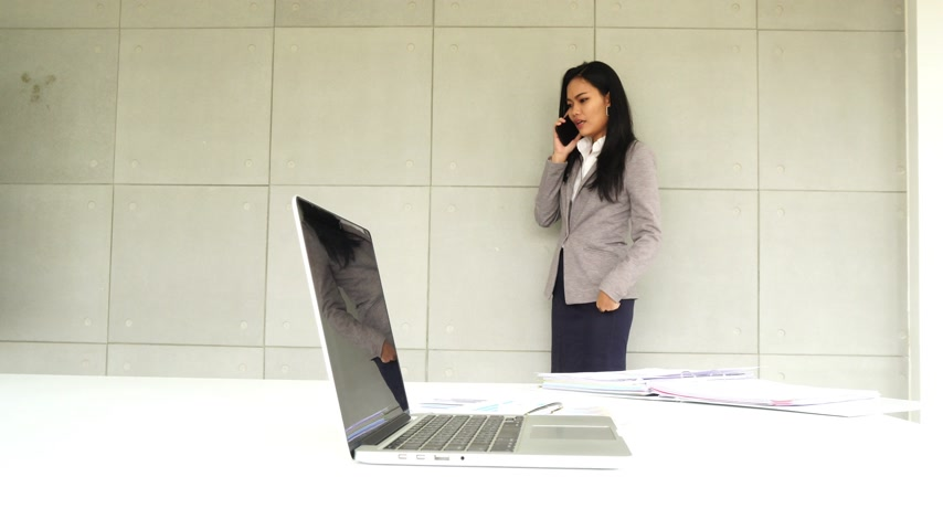 Asian business female working with smartphone and review document at office building, call phone communicate to somebody
