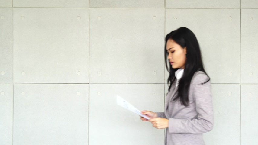 Asian business female stand at office building and read document paper