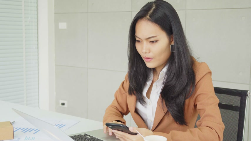 Smart Asian business female working online with smartphone at office building