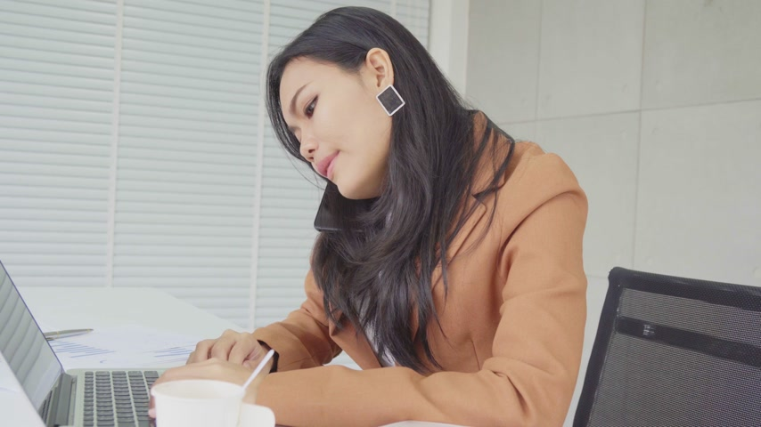 Asian business woman busy in work with laptop computer and call phone to somebody