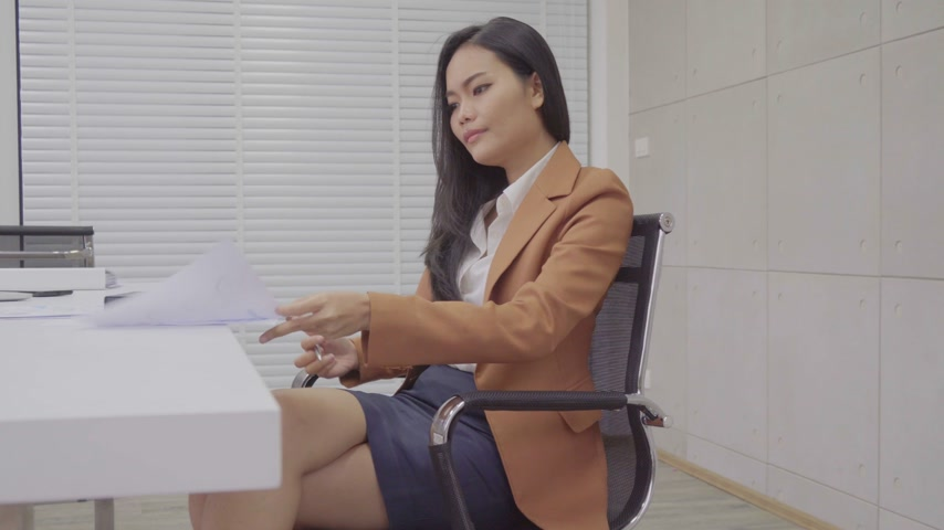 Asian business female work and read document  at office building