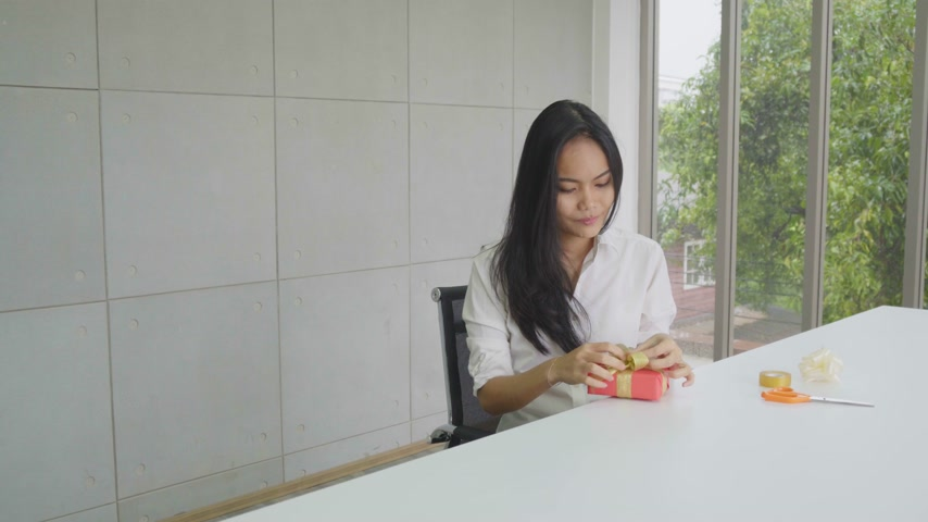 Asian woman is wrapping up a present for Christmas or New Year Wideo