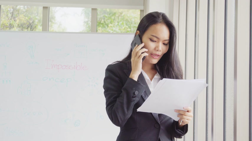 Asian business female call phone communication and read document  at office building