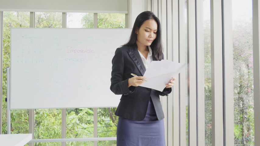 Asian business female stand at office building and read document
