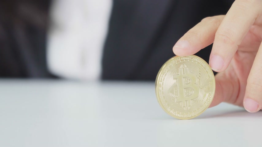 woman is pick and show bitcoin token on table in workplace