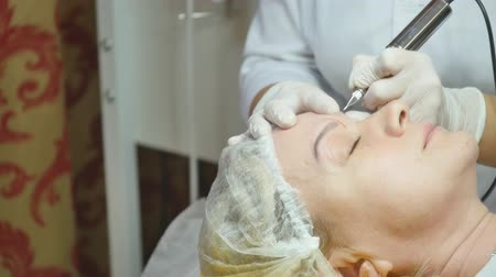 kaşları : Cosmetologist making permanent makeup on womans face Stok Video