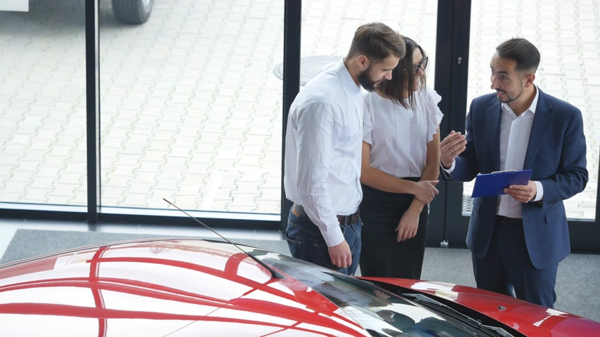 sprzedawca : Top view of young male consultant and buyers signing contract for new car in auto show. Concept for car rental
