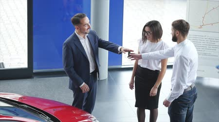 аренда : Top view of young male consultant and buyers signing contract for new car in auto show. Concept for car rental