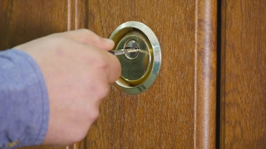 locksmith : Locking up or unlocking door with key in hand