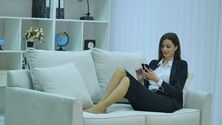 bizneswoman : Charming beautiful business woman casual style using, chatting, connecting, social, calling and watching smartphone is sitting on sofa. Wideo