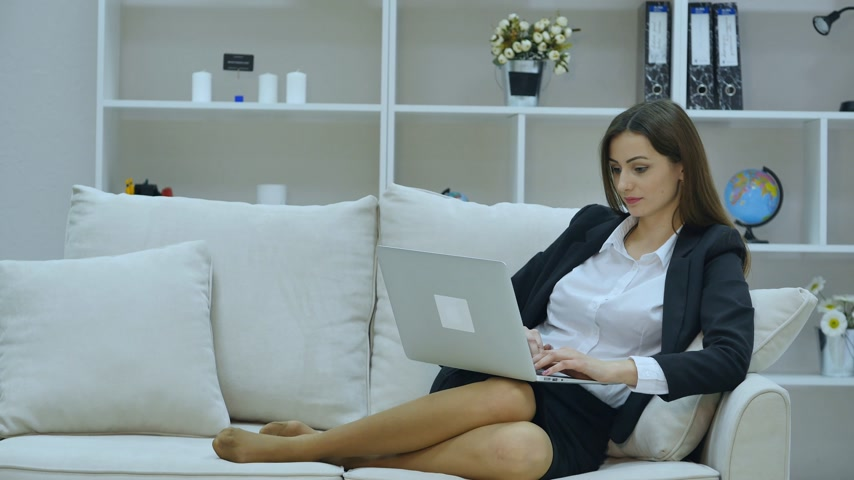 kanapa : Young businesswoman sitting on sofa, working with laptop computer Wideo