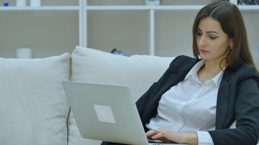 bizneswoman : Young businesswoman sitting on sofa, working with laptop computer Wideo