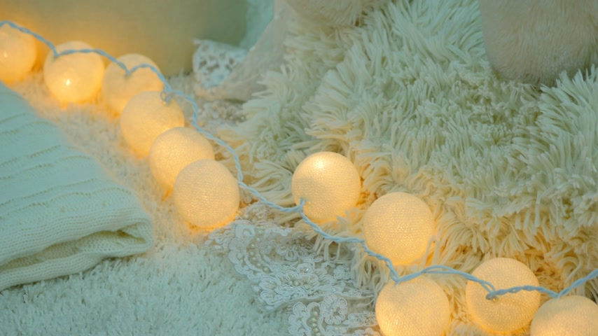 otthonos : A stack of white and beige pillows and blankets with string lights on vintage wooden chair. Cozy interior details, soft and warm home decor