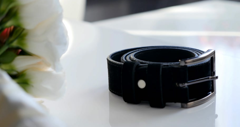 носить : Black leather belt for trousers on a white table Стоковые видеозаписи