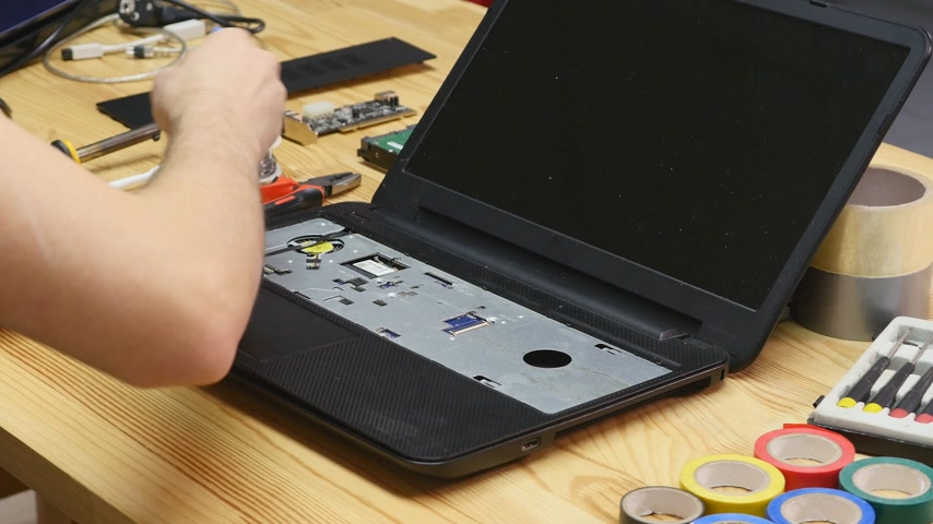 inventing : Male engineer disassembles a laptop with a screwdriver. Wooden table top view