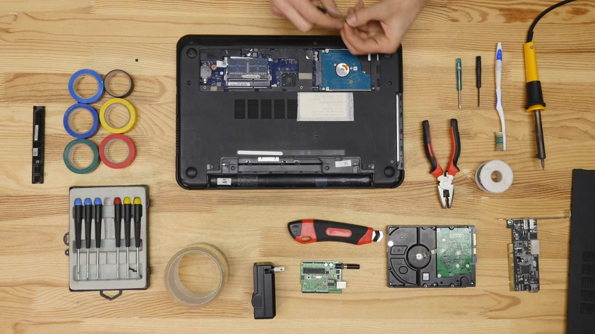inventing : A man disassemble a laptop with a screwdriver. Wooden table top view. Timelapse